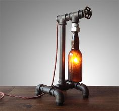 This lamp is constructed from industrial style black iron piping. The vintage bottle is firmly secured by custom rubber gaskets that grasp the bottle without causing damage. A low wattage bulb is used… Industrial Furniture, Vintage Industrial, Industrial Style, Furniture Fittings, Steampunk Furniture, Industrial Irons, Pipe Furniture, Furniture Dolly, Industrial Lighting