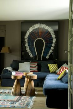 framed Native American war bonnet, grouped tribal stools and pops of colour by designer Elodie Sire of D.Mesure