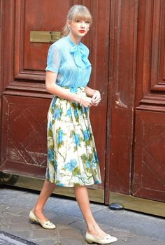 Taylor Swift rocks a vintage look with a pleated blouse, floral print skirt and neutral flats to finish off the outfit.