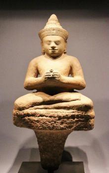 Bouddha au doux visage souriant d?aspect juvénile, coiffé d?un diadème surmonté de l'ushnisha. Il est assis en Virasana sur un tertre quadrangulaire, les mains jointes tenant la conque à eau lustrale. Très Belle sculpture en grès dur, (le tertre est supporté par un épi d'encastrement de socle). Art Khmer, région de LOBPURI XII-XIII eme s. Ht: 66 cm.