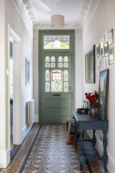 Farrow & Ball Ammonite grey on the walls and Pigeon on the front door, combined with the original Edwardian floor tiles and vintage console & mirrors make the entrance hallway of this Edwardian house in South London feel grand but welcoming. Interior Design by www.imperfectinteriors.co.uk Photos by Chris Snook
