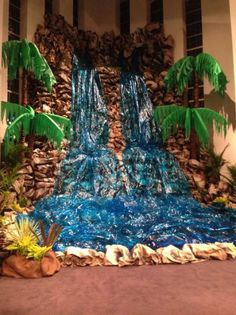 Waterfall made from kraft paper stapled to cardboard and spray painted. Cellophane and lights for the water. Palm trees made out of carpet rolls and the leaves are cut pool noodles wrapped with table clothes: Deco Jungle, Jungle Party, Safari Party, Jungle Theme, Jungle Safari, Cave Quest Vbs, Off The Map, Vbs Crafts, Vacation Bible School