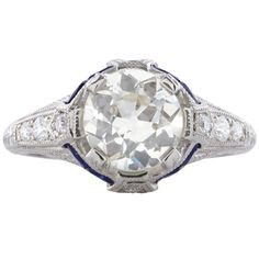 Art Deco Style Platinum Ring features a 1.56 carat Old European Cut Diamond. Accenting the center stone are 8 Round Full Cut Diamonds totaling 0.17 carats, & 8 blue sapphires totaling approximately 0.40 carats. The ring mounting is detailed with milgrain edges & engraved scrollwork. Ring size is a 5.25 & weighs 5.8 grams total.