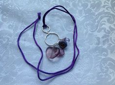 Purple Cluster Necklace Handmade silver plated swirl with a cluster of purple glass beads on a satiny purple cord.
