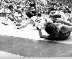 Black and white photo of five University of Oregon basketball players scrambling on the floor for a loose ball in a game against UCLA at McArthur Court on February 22, 1973, and lost by the Ducks 61-72. From left: Ronnie Lee, Doug Little, Gerald Willett, Mark Barwig, and Ernie Kent. ©University of Oregon Libraries - Special Collections and University Archives