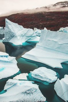 Greenland. Icebergs get trapped in a narrow channel between Rødeø Island (Red Island  named for the red old Devonian sandstone)  and Milneland, Scoresby Sund. Water lines show that history of theses icebergs on their journey, tumbling and turning.  Photography - Katja Riedel