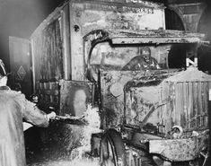 A fireman puts out a fire in a burning truck, but it is too late to save the driver circa 1940.
