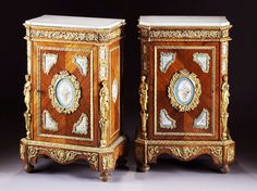 A Very Fine Pair of French Napoleon III Figural Ormolu and Porcelain (Probably Sevres) Mounted Tulipwood Meuble A Hauteur D'Appui. The rectangular shaped body fitted with a white marble top on canted corners. The reticulated frieze of scrolling grapevine and clusters interspersed with doves and centering paired squirrels. The front hinged door trimmed in acanthus cast encadrements enclosing central bleu celeste oval porcelain plaque of a ribbon-tied floral basket within a border of parcel…
