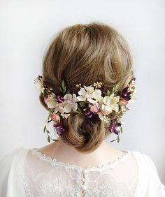 A floral garland with trailing vines, adorned with wildflowers and small cabbage roses. Color palette is a romantic combination of cream/off-white, light coral, eggplant purple and gold. Pearl details throughout. The length is about 13 end to end. It requires several hair pins inserted