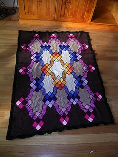 "From the description: Careful color selection gives this afghan the look of luminescence. Slip stitch the ""leading"" in black to complete the look."