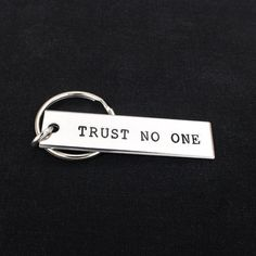 "This ""Trust No One"" key chain is hand stamped with care, one letter at a time. This key chain is stamped on a x aluminum blank. The rectangles are made out of Pure 1100 Aluminum, which is food"