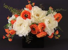Artificial silk flowers arrangement.White peonies,orange ranunculus,sweet pea and foliage in black glass vase.Design by Simone Vartan.