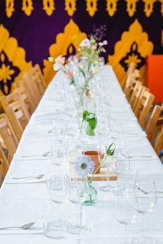 Detail van de romantisch gedekte tafel tijdens een tuinbruiloft. Het diner vond plaats in een ruime tent in de tuin, waar het bruidspaar eerder die dag ook getrouwd was.