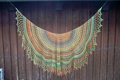 It is a semi-circle shawl worked from top-down. Size H hook was used on the self-stripping yarn with white border. Size G hook was used on the second one with black border. 3 cobweb yarns were held together to crochet the body and 2 black yarn held together for the border. This pattern will work with any kind of yarn and colours. Gauge is unimportant.