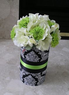 Rehearsal dinner centerpiece - use red instead of green, can easily make these out of paper-wrapped glass jars. White sweetpeas and red carnations.