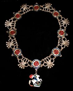 The collar of the Order of the Garter. The original garter of of gold and enamel of twenty one garters containing a red rose.  The garters are enamelled blue with gold letters – giving the motto of the order HONI SOIT QUI MAL Y PENSE  meaning:  The shame be his who thinks ill of it.  The garter links alternate with a double gold knot in the fashion of a cord with four tassels at the end.  The original collar measures 1562mm in length and weighs 33oz. Our replica has only eight garters