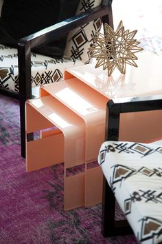 A trio of peach colored nesting tables between two tribal print chairs