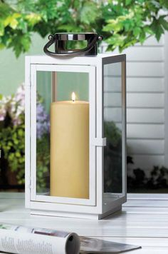 "Candleholders & Candles Home Locomotion Enclose your favorite candle with this sleek metal and glass lantern. The simple metal framework is painted white and holds four clear glass panels to let the light shine bright. Its trimmed with a silver top and braided rope hanging handle. Candle not included. 14 1/2"" high with handle. Item weight: 2.60lbsItem dimensions: 5.75"" W x 11.25"" H x 6.00"" LMaterials: Iron, GlassUPC: 849179020613"