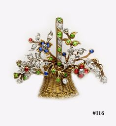 Demantoid garnet, Burma ruby, sapphire, diamond gold and platinum flower basket brooch.  This very pretty brooch is made of intricate gold wire woven to make the basket with a wonderful splay of diamonds, rubies, sapphires and demantoid garnets in yellow gold and platinum.