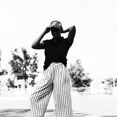 Black and white casual chic women's fashion with dad hat and pinstripe trousers