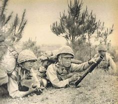 """Two Japanese soldiers preparing to fire a type 89 grenade discharger, otherwise known to Americans as """"the Japanese knee mortar."""" The Japanese high command quickly noted that grenades could be deadly in combat but lacked one thing: range.  To solve this problem the Japanese created the knee mortar, a type of light mortar that could effectively launch grenades from about 120 meters. It could fire incendiary, high explosive, fragmentation, and even smoke grenades and shells.  The  mortar was…"""
