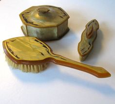This beautiful antique Bakelite/celluloid vanity set is a wonderful piece of Hollywood Glam. The set includes a hair brush, fingernail buffer and power box. Each has a delicate Art Deco design on the top.  The items are in age appropriate condition. There is some cracking on the ends of the buffer and the buffer itself is hardened due to age.  Beautiful set on an antique dresser. Great stage prop and always a great gift!  If you would like more than one item, combined shipping may allow you…