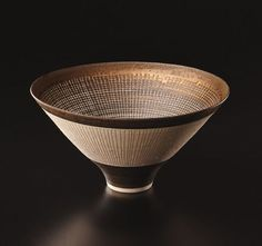 Lucie Rie. Large conical bowl, ca. 1978. Porcelain, bright golden manganese glaze with concentric rings of sgraffito and inlaid grid designs. 8 5/8 in. (21.9 cm.) diameter.