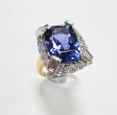 Sale F170615 Lot 356  An impressive tanzanite and diamond ring, the rectangular cushion cut intense violet tanzanite held by four trapezoid diamond set claws above a border of round brilliant cut diamonds, in white to a plain band of yellow precious metal, stamped '18k', size E; estimated weight of tanzanite 6.65cts, estimated total weight of diamonds 1.10cts  - Cheffins