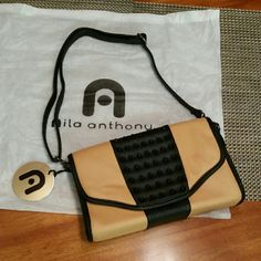 Black and Camel Brown Nila Anthony Purse. Black and Camel Brown Nila Anthony purse with black studded detail. Still has tags on it! Brand new! Shoulder purse but the strap is adjustable to also use as a cross-body. 7 1/2 in. Tall. 11 1/2 in. Long. 2 1/2 in. Wide. Nila Anthony Bags Shoulder Bags