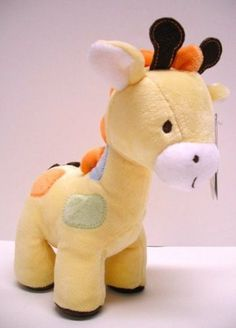 Child of Mine Carters Plush Giraffe by Carters. $25.00. Filled with polyester fiberfill and some plastic pellets. Small soft plush giraffe with embroidered facial features and felt horns. Orange, green and blue stitched on spots with an orange velour mane and brown bottom of the feet.