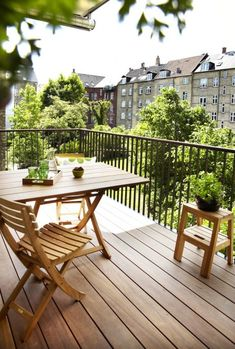 A simple urban balcony garden with light wood furniture.