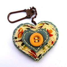 handbag charm, key chain, keyfob or zipper pull.    A hand sewn heart shaped charm with layers of green felt and peach floral fabric.  The centre piece of the charm is a wooden button  Each layer has been handstitched in a cream embroidery thread and the largest heart has been hand blanket stitched to another for stability. swivel clasp has been securely sewn between the two hearts so you can attach to your handbag, zipper