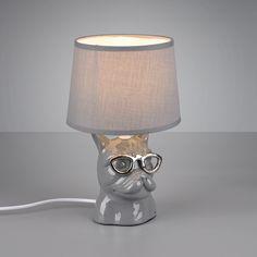 Lampka nocna DOSY R50231011 to ceramiczna podstawa w kształcie psa w okularach w kolorze popielatym oraz abażur z tkaniny o tej samej barwie. Lampka będzie ciekawą dekoracją wnętrza, nie tylko pokoju dziecięcego. Lampka posiada przełącznik na kablu. W serii DOSY dostępne są także inny kolory.