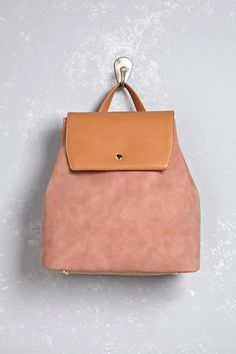 A faux leather backpack featuring contrast trim, a top handle, dual adjustable shoulder straps, a snap-button top closure, exterior snap-button extenders, an interior zip pocket, an interior slip pocket, and high-polish feet. This is an independent brand and not a Forever 21 branded item.