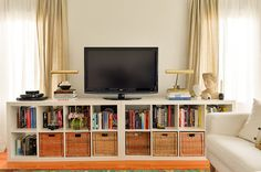 Here a pair of simple Ikea shelving units makes a long, low base for a flat-screen TV. Neatly arranged books and baskets below, and pairs of library lamps and floaty curtains above, help move the eye around the space.