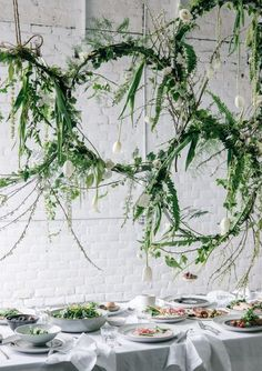 These hanging greenery hoops prove a nonfloral centerpiece can be just as pretty as a classic rose arrangement. Decorated with fern leaves and vines, these hanging centerpieces bring a little vibrancy to a minimalist tablescape. The tulip accents are especially fitting for a spring wedding.