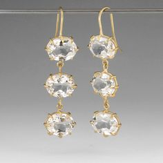 """18k gold triple drops faceted white oval topaz earrings. They measure 1.75"""" long and 0.5"""" wide."""