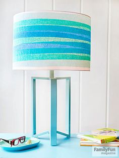 Match your lamp shade to your decor, for cheap. Starting at the bottom of a plain shade, simply wrap lengths of streamer around it, securing the ends with double-sided tape.