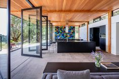 Living Room, Stools, Limestone Floor, Sofa, Recessed Lighting, and Console Tables Reclaimed Douglas fir lines the 11-foot-tall ceilings, while stone-tiled floors with built-in radiant heating are located underfoot. Photo 8 of 14 in This Elegant Californian Prefab Minimizes Site Disturbance