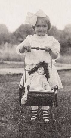 Antique photo of little girl with her doll in baby buggy / pram, circa 1910.