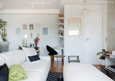 Sala de estar e home office integrados com decoração em tons neutros.