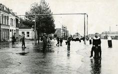 Fotocollectie, Hoofdstraat, Zuid (De Gorzen), Breur, Chr., ja, 19611103, Hoog water in de Hoofdstraat is voor de jeugd een bron van vermaak. Rechts de Voorhaven., Foto
