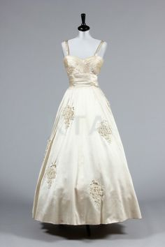 A Maison Worth couture ivory satin bridal gown, late 1950s, labelled, crossover pleats to bodice and broad waistband, the skirt applied with bouquets of opalescent celluloid flowers with bugle beaded stems and ribbon ties, two floating panels at the rear skirt,