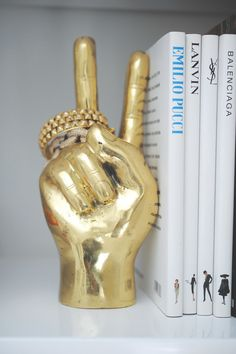 A peace sign sculpture doubles as a bookend and jewelry organizer