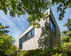 House in Chelsea, Quebec    The exterior of this house in Quebec is made from industrial concrete blocks. But instead of a running bond or some other stacked pattern, Kariouk Associates composed the blocks into a pinwheel pattern. It makes the boxy exterior appear woven.