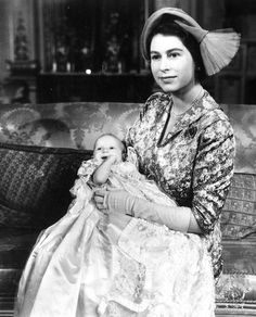 Princess Elizabeth, in a jaunty hat, shows off her new baby daughter, Princess Anne, on the day of her christening in October 1950. The lace christening gown is a royal family heirloom, and was originally worn by Queen Victoria's eldest daughter in 1841, as well as by Elizabeth herself.