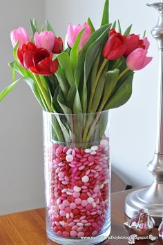1/10/13 centerpiece for my Valentine's tablescape. Tulip and valentine M's vase - place a smaller glass vase inside a larger one. Fill the gap with M's.