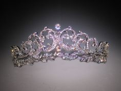 Created in 1936 by Cartier, the Halo Scroll tiara was purchased by Prince Albert for his wife, the Queen Mother Elizabeth, who only wore it a few tines. After ascending the throne, as Queen Mother she had access to the Royal vaults (& the spectacular tiaras inside).  So, she gifted the Halo to her daughter (& future queen) Elizabeth on her 18th birthday. Queen Elizabeth has never worn it publicly, instead lending it to her sisters to enjoy.