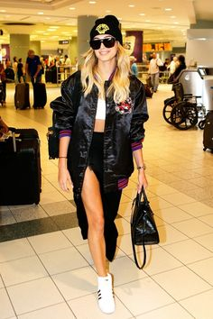 SneakerHailey Baldwin takes on the paparazzi at the airport in a bomber, bra,  a high waisted skirt with a slit and sneakers