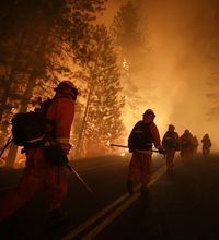 A massive fire burning near Yosemite National Park continued its spread Sunday. More campgrounds were evacuated and firefighters worked to protect ancient giant sequoia groves. The fire was within a mile of the reservoir that supplies water to more than 2.6 million people in the San Francisco Bay area.
